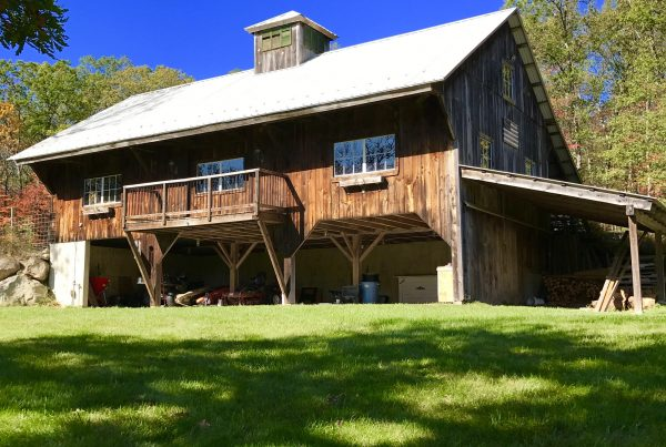 Hand crafted custom timber frame barn with beautiful deck and overhang