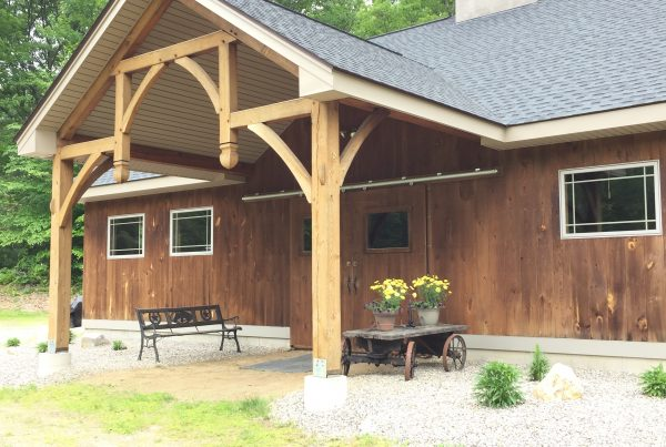 Front of Timber Frame Barn with bench and yellow flowers